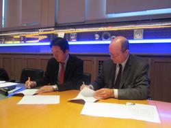 Нобусуке Иваи (слева) и Эрве Амело (справа) подписывают договор о сотрудничестве в головном офисе Моtul Обервилье